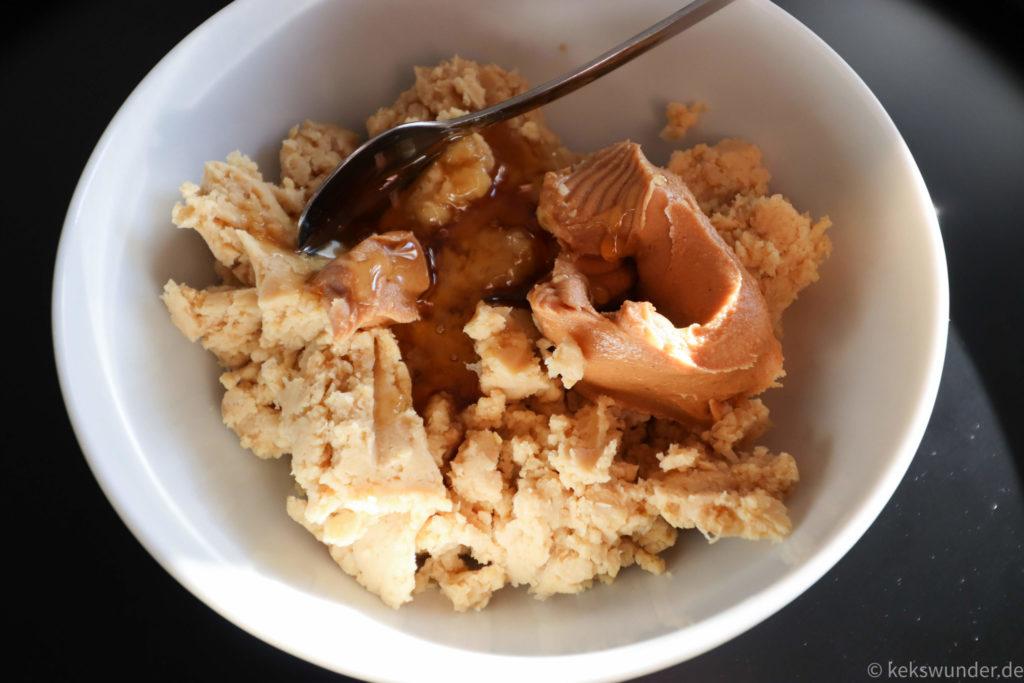 Kichererbsen mit Honig und Erdnussbutter in weißer Schale mit Löffel